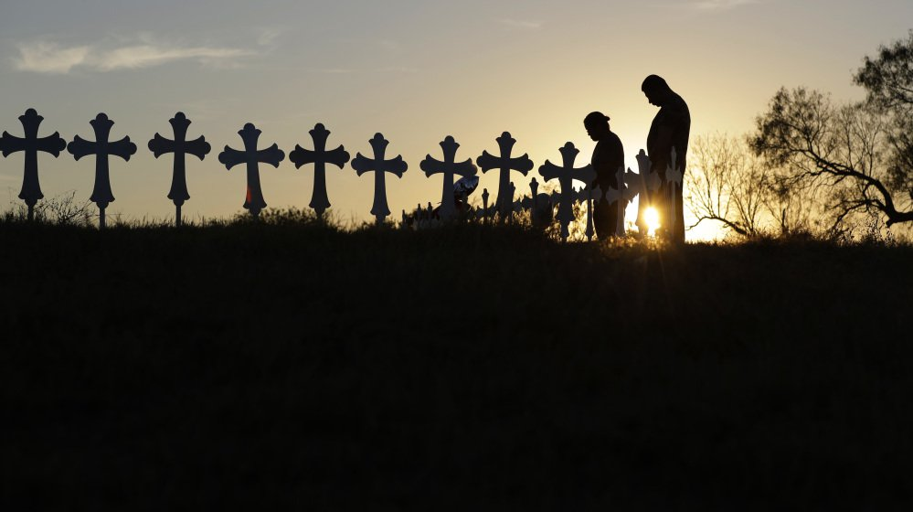 Kenneth and Irene Hernandez pay their respects as they visit a makeshift memorial with crosses placed near the scene of a shooting at the First Baptist Church of Sutherland Springs, Texas, in November, 2017.