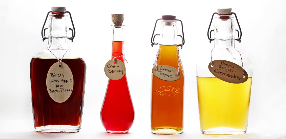 Simple syrups, from left, birch with apple and black pepper, cran-rosemary, lemon thyme, and honey ginger clementine.