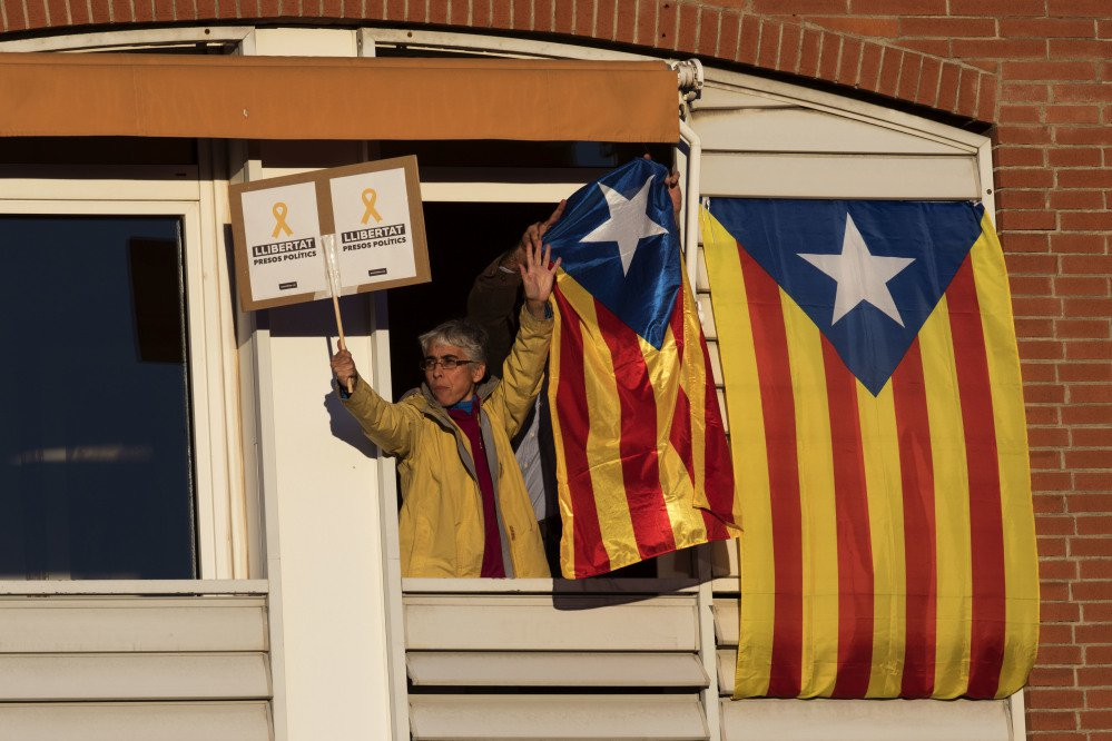 People watch from a balcony as demonstrators take part in a protest calling for the release of jailed Catalan politicians in Barcelona, Spain, on Saturday.