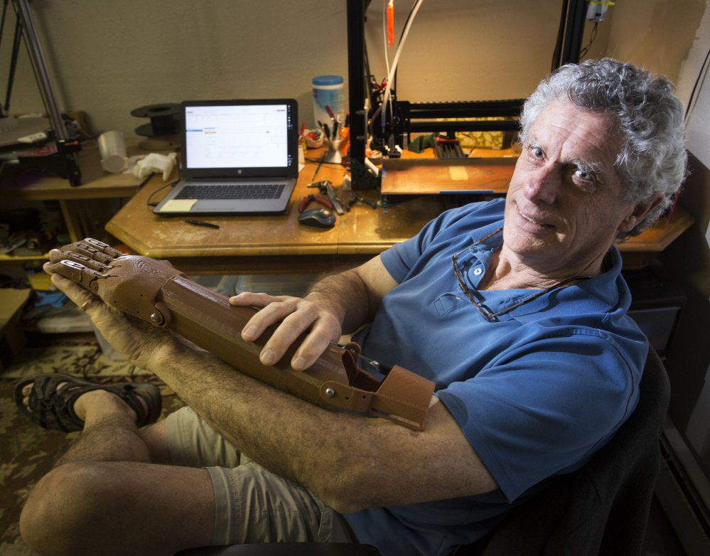 Dean Rock volunteers his time and money to make prosthetic forearms using a 3D printer in the basement of his Cumberland Center home. Most of his work has ended up in the Dominican Republic.