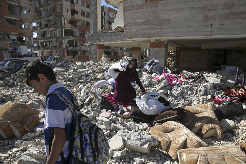 An earthquake survivor carries her belongings Tuesday over debris in front of her house, in a compound which was built under the Mehr state-owned program, in Sarpol-e-Zahab in western Iran. Iran's President Hassan Rouhani says his administration will probe the cause of so much damage to buildings constructed under the state-owned program after a powerful earthquake hit the area along the border with Iraq on Sunday which killed over 400 people.
