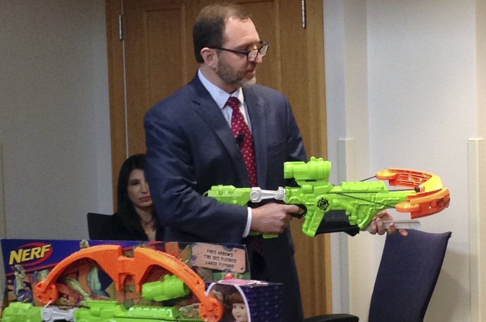 "James Swartz, director of World Against Toys Causing Harm, or WATCH, displays Nerf's ""Zombie Strike"" crossbow during a news conference Tuesday in Boston, where the child-safety group released its annual holiday list of the 10 most hazardous toys."