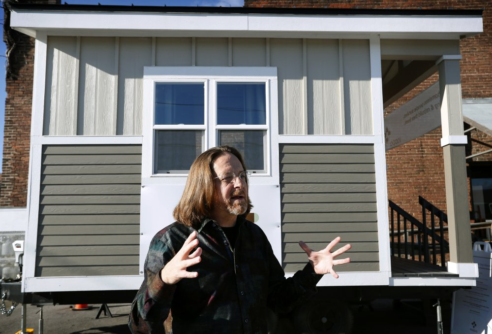 """Joe Stevens stands in front of one of the tiny homes his student group built in hopes of helping the homeless in Des Moines, Iowa. """"We're not giving up,"""" he said."""