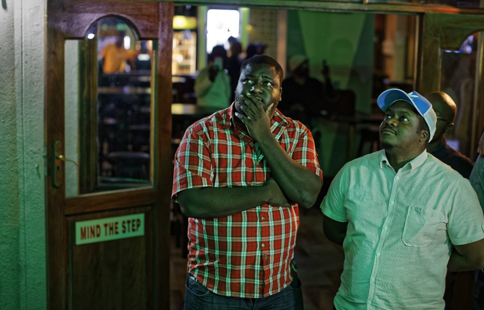 Disappointed Zimbabweans watch a televised address to the nation by President Robert Mugabe at a bar in downtown Harare on Sunday. Mugabe baffled the country by ending his address without announcing his resignation.