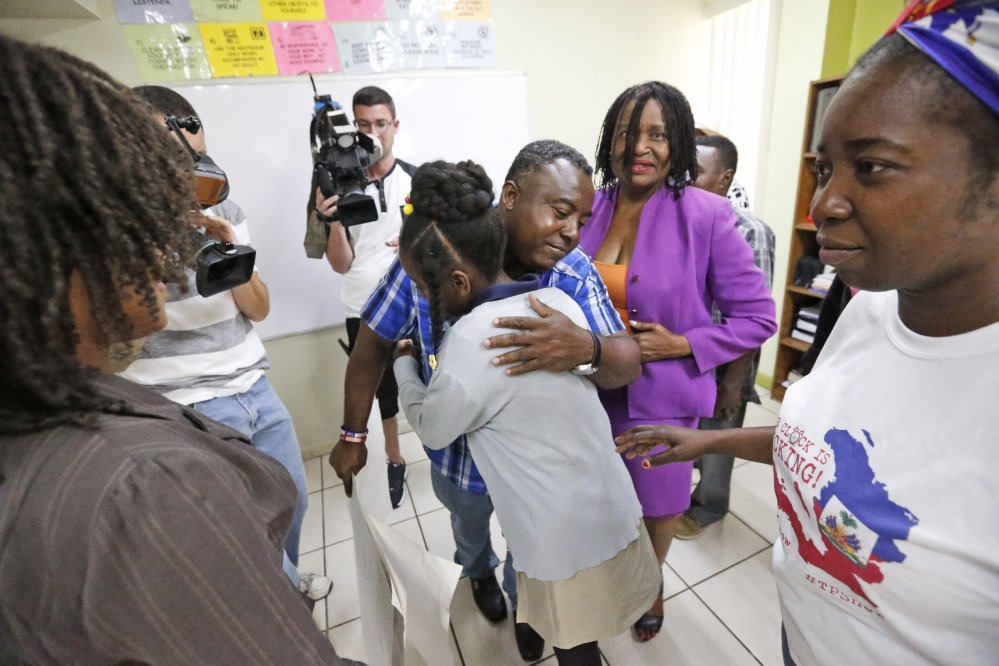 Pierrot Mervilier, center rear, hugs a girl who did not wish to be identified, living in the U.S. with Temporary Protected Status after she and her family spoke to members of the media in Miami, in May. The Trump administration said Nov. 20 it is ending a temporary residency permit program that has allowed almost 60,000 citizens from Haiti to live and work in the United States since a 2010 powerful earthquake shook the Caribbean nation.