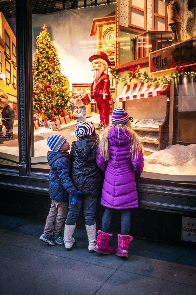 Children look in Macy's storefront window in New York City on a chilly evening. Inside, they can make a reservation to visit Santa.
