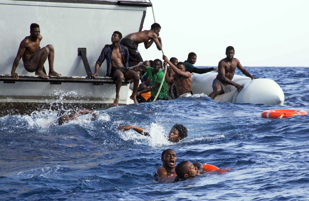 Migrants from a dinghy try to board a Libyan coast guard ship during a rescue operation off the coast of Libya Nov. 6. Researchers have linked some migration to climate change.