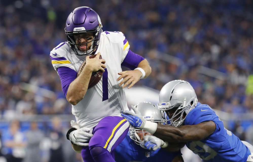 Minnesota quarterback Case Keenum, left, pulls away from the Detroit defense to score on a 9-yard rush in the first half on Thursday. The Vikings won, 30-23.