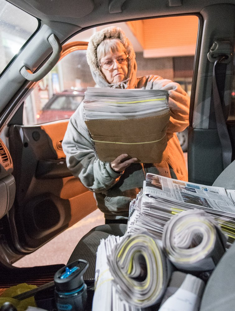 "Kay Brackley loads bundles of newspapers she picked up in Farmington on a Saturday. ""You do it night after night and you know what lights are on at houses and what cars are in the yard,"" she said. ""You get to know your customers."""
