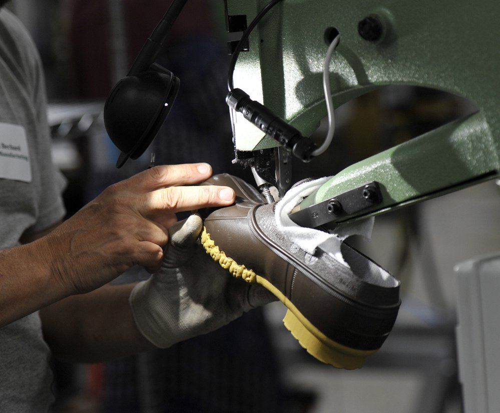 "Gerard Bechard trims the bottom of L.L. Bean's popular ""duck boot"" at the firm's production plant in Lewiston. The retailer expects to sell 750,000 pairs this year."