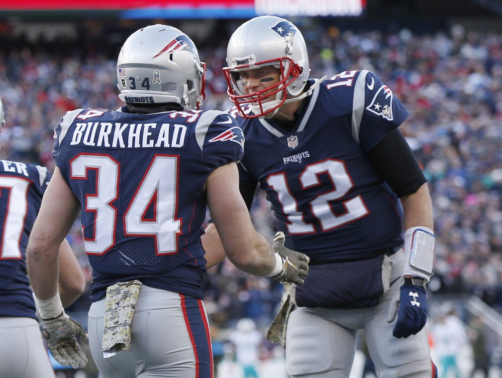 New England Patriots quarterback Tom Brady, right, celebrates his touchdown pass to running back Rex Burkhead during the first half of the Patriots' 35-17 win over the Miami Dolphins on Sunday in Foxborough, Massachusetts.