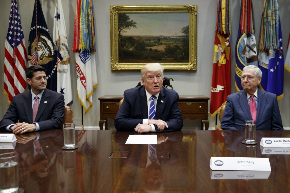 House Speaker Paul Ryan, R-Wis., left, and Senate Majority Leader Mitch McConnell, R-Ky., right, listen as President Trump speaks during a meeting with Congressional leaders and administration officials on tax reform. A new CBO scoring of the bill shows it will hurt poor Americans more than previously believed.