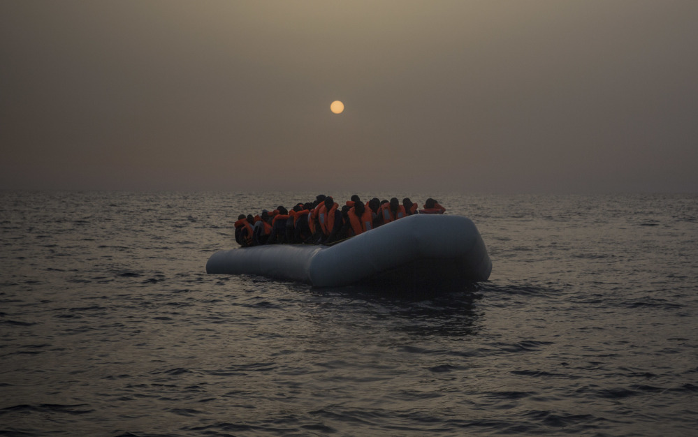 African refugees and migrants, mostly from Sudan and Senegal, wait for assistance off the Libyan coast in February. Hundreds of thousands of migrants are facing an uncertain future.