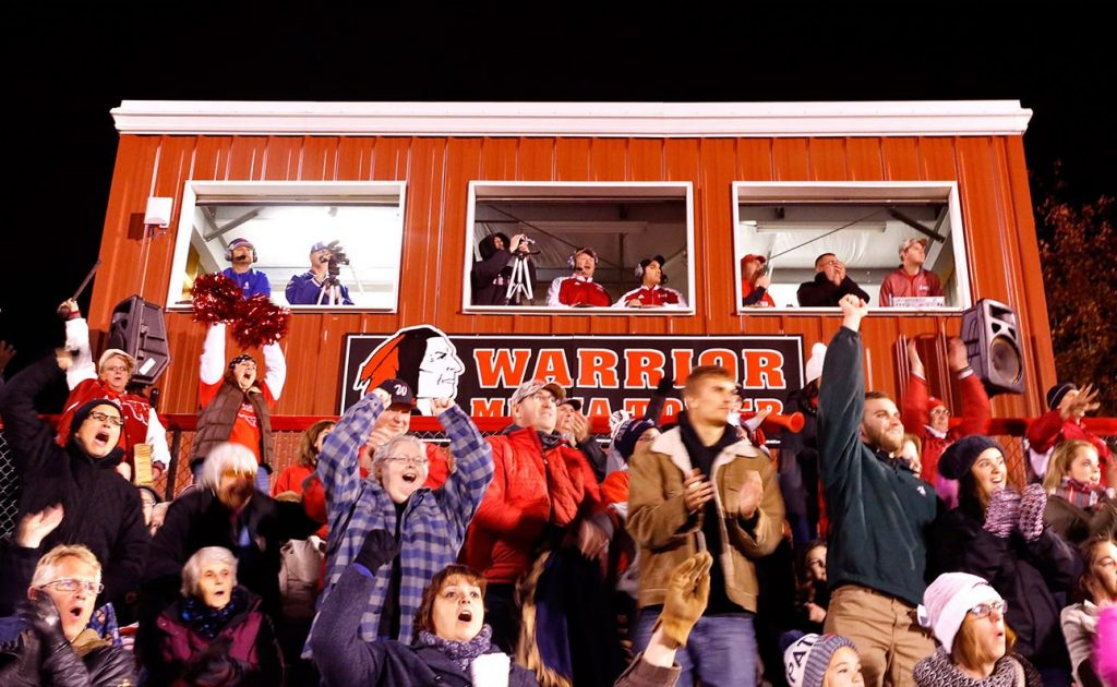 A Native American-themed logo adorns the Wells High School press box behind a crowd of cheering fans during last Friday's game between the Wells Warriors and Oak Hill.