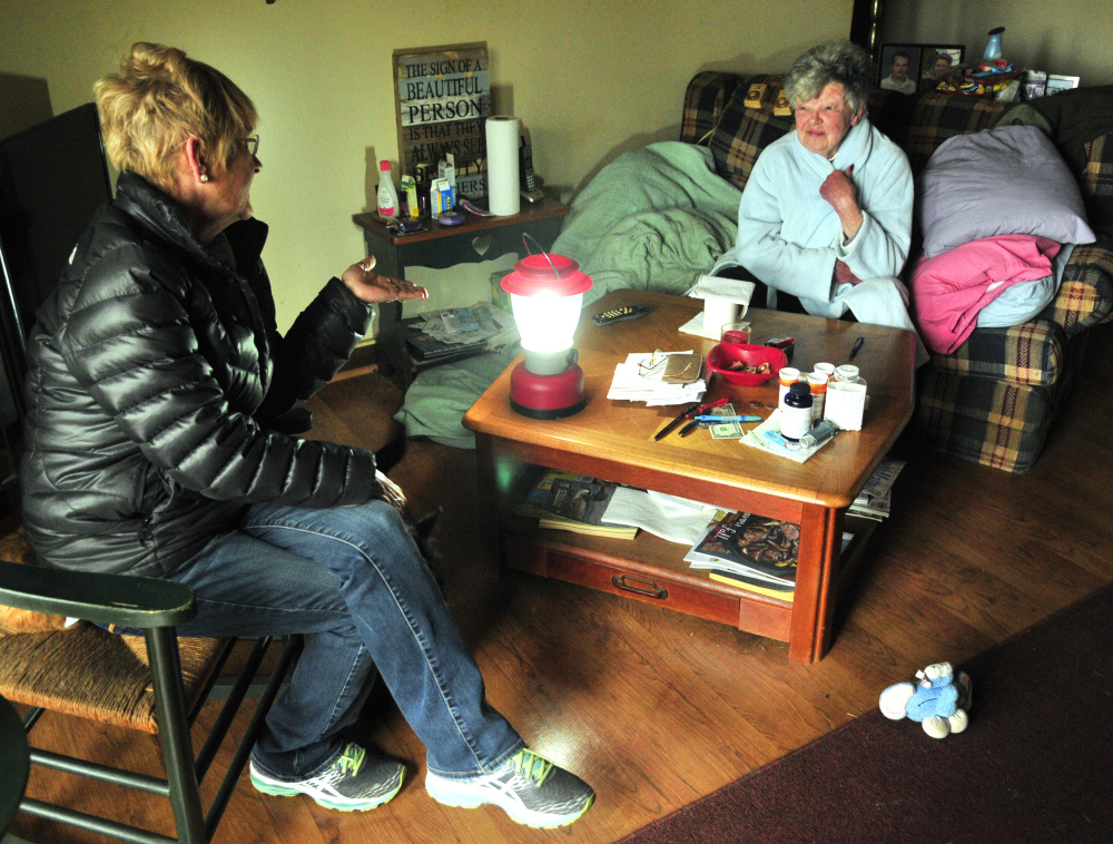 Karen Anderson, left, visits with her neighbor Leona Russell on Wednesday in Farmingdale's Hayford Heights neighborhood ,which was still without power. Anderson, who has been bringing Russell meals, brought over the lantern to lend it to her.