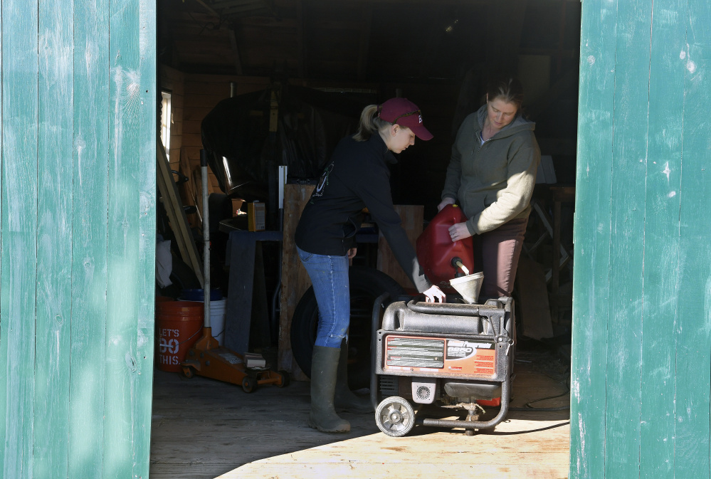 Emma Christman, 17, helps her mother, Jana, fuel a generator Tuesday in the shed at their Litchfield home. Most homes in the town were still without power after Monday's storm.