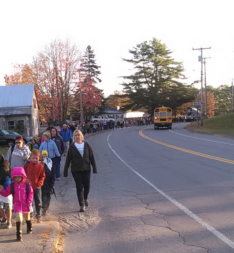 Patti Theberge, a first-grade teacher at Carrabec Community School, takes the lead as a trail of students, which goes back   mile, walk from Carrabec High School to the community school during its October Walking School Bus event.