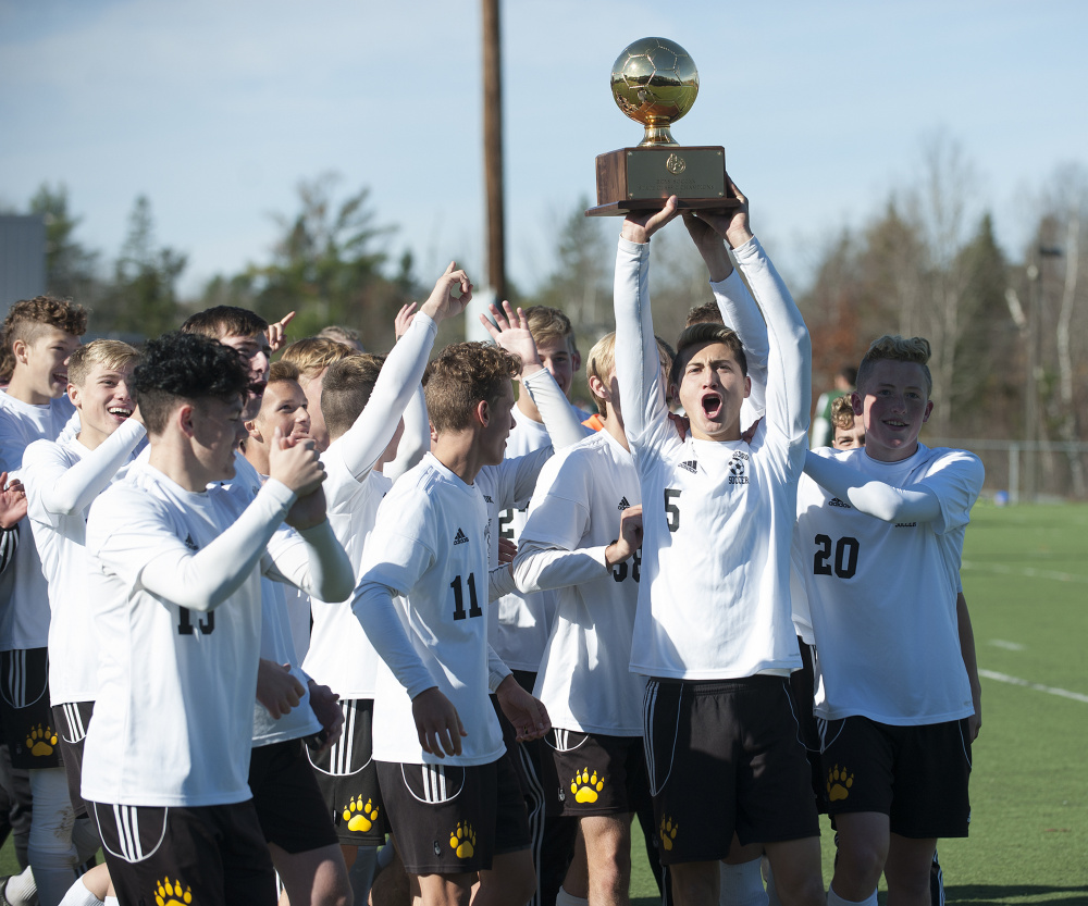 The Maranacook boys soccer team celebrates with the Gold Ball after it defeated Fort Kent 1-0 in the Class C state championship game Saturday morning at Hampden Academy.
