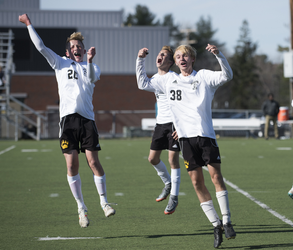 Maranacook players Duncan Rogers, left, Wyatt Lambert, center, and Bryan Riley celebrate Silas Mohlar's goal with 20 seconds left in regulation of the Class C state final against Fort Kent on Saturday morning at Hampden Academy.