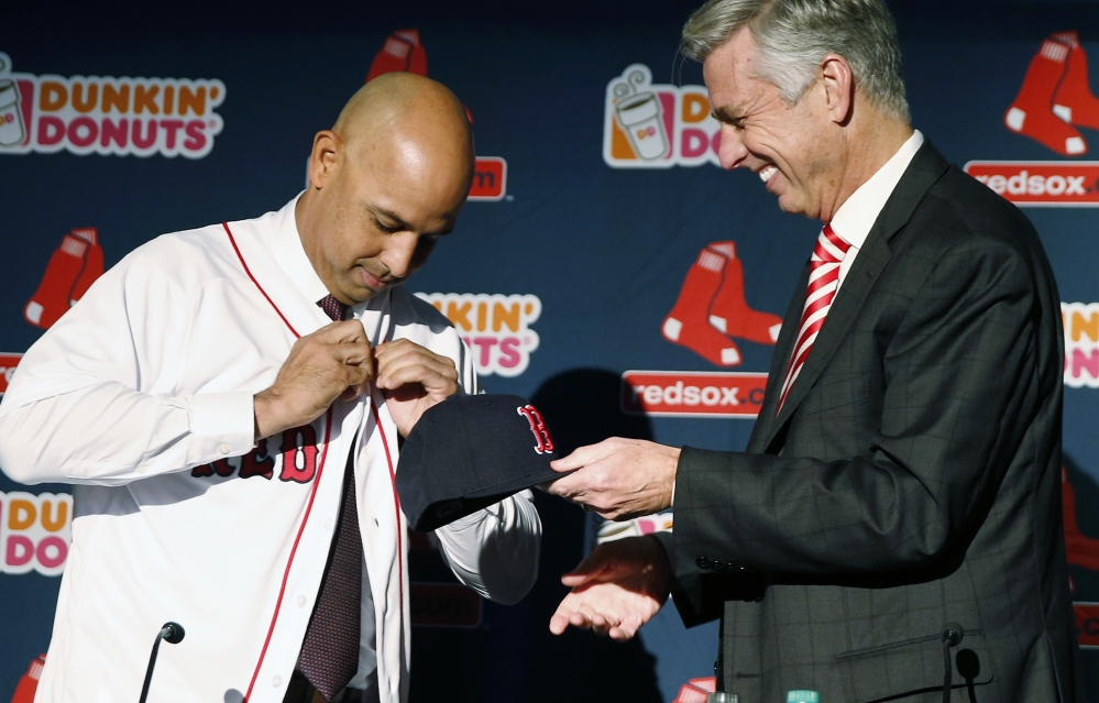 Alex Cora, left, buttons his jersey as he is introduced as new manager of the Boston Red Sox by President of Baseball Operations Dave Dombrowski during a news conference Monday in Boston.