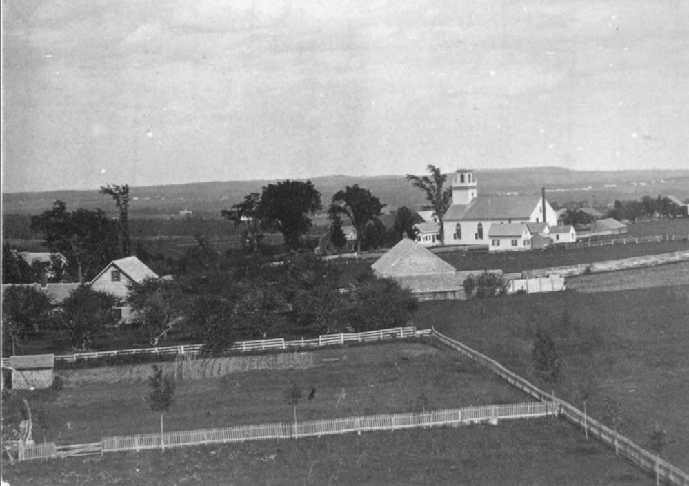 From the tower atop Bearce Hall at Kents Hill School before 1872, looking east over Kents Hill Village. Torsey Methodist Church can be seen in the foreground and in the distance is Readfield Depot.