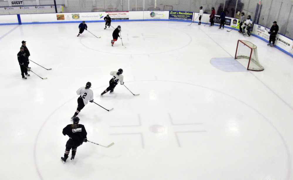 Winslow/Gardiner girls hockey players loop around the faceoff circles during a drill Tuesday night at the Camden National Bank Ice Vault in Hallowell.