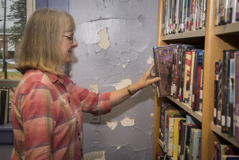 Lynn Howker, Monmouth Middle School librarian, returns a book to the shelf recently next to a library wall with chipped and cracked paint. The library is housed in a century-old building.
