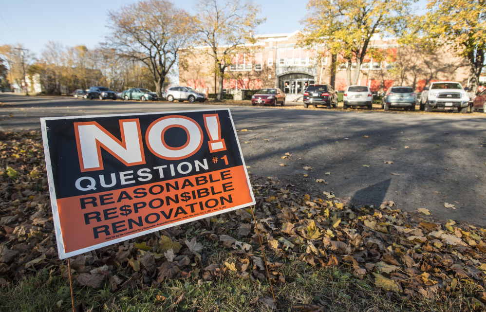 "A political sign urging voters to vote ""no"" on local Question 1 stands across the street from Winslow Junior High School on Wednesday in Winslow."