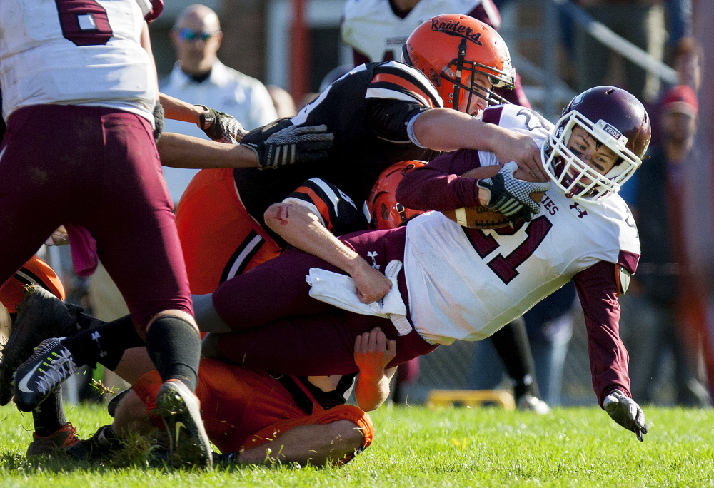 Winslow's Isaiah Goldsmith, center, brings down Maine Central Institute's Will Russell during a Class C North semifinal game last Saturday at Poulin Field in Winslow.