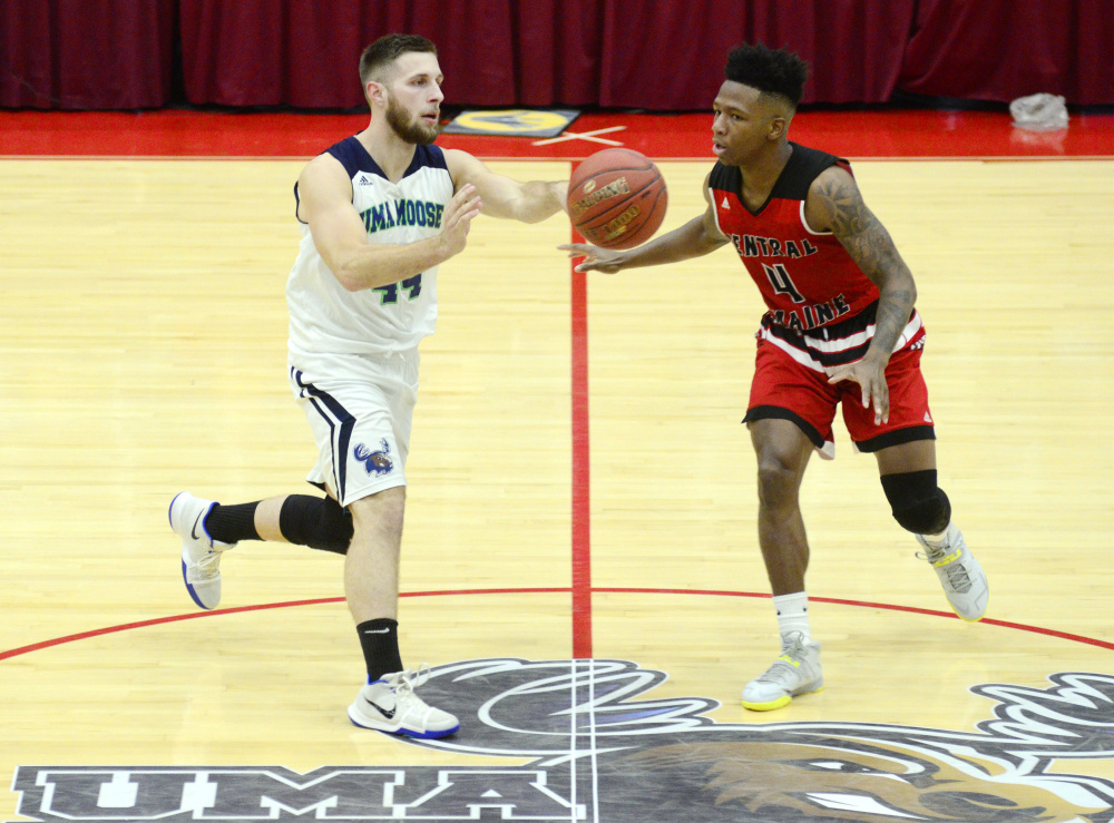 University of Maine at Augusta guard Jordan Holmes, of Oakland, left, passes  in front of Central Maine Community College defender Akeem Laurie during a game Wednesday at the Augusta Civic Center.