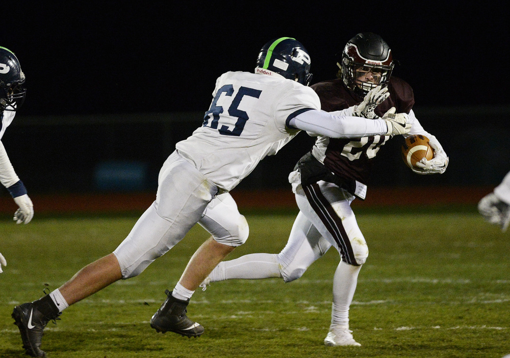 Windham's Tanner Bernier carries the ball as Portland's Jonah Green moves in during the Class A North football championship Friday night at Windham High.