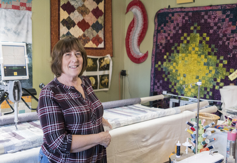 Lynn Irish, owner of WhipperSnappers Quilt Studio in Hallowell stands next to a long arm quilting machine on Saturday. She is preparing to move her shop at 109 Water St. to a the former location of Buddy's Diner. Irish says her new shop will double in size.