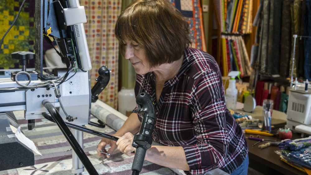 Lynn Irish works on her long arm quilting machine Saturday at her shop on Water Street in Hallowell. Irish is planning on moving a few doors down from the current location, doubling her space and providing the opportunity for more classes and workshops.