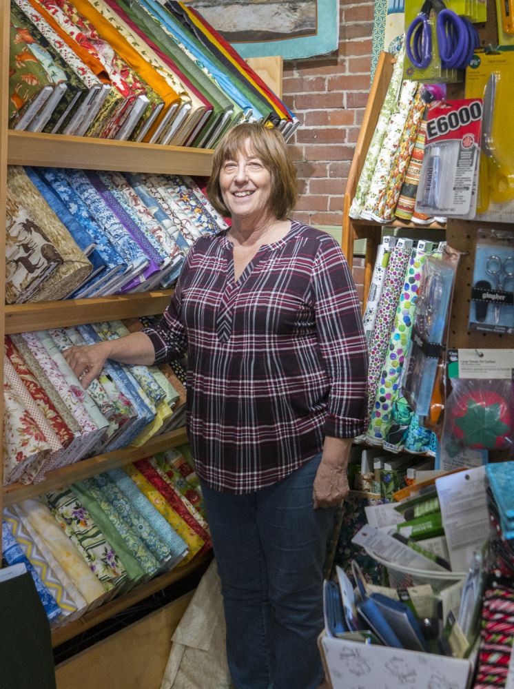 Lynn Irish, the owner of WhipperSnappers Quilt Studio in Hallowell stands amid bolts of fabric Saturday in her shop on Water Street. She is preparing to move and hopes to be open in the new space in early December.