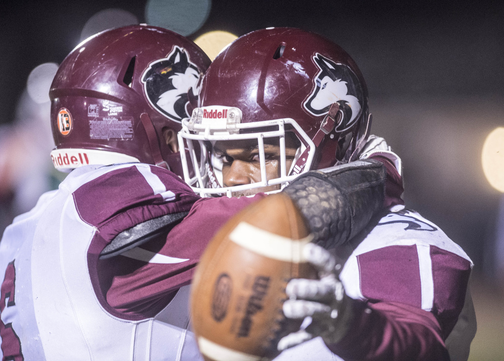 Maine Central Institute's Pedro Matos, right, celebrates his first quarter touchdown against Mt. Desert Island with teammate Adam Bertrand during the Class C North title game Saturday night in Bar Harbor.