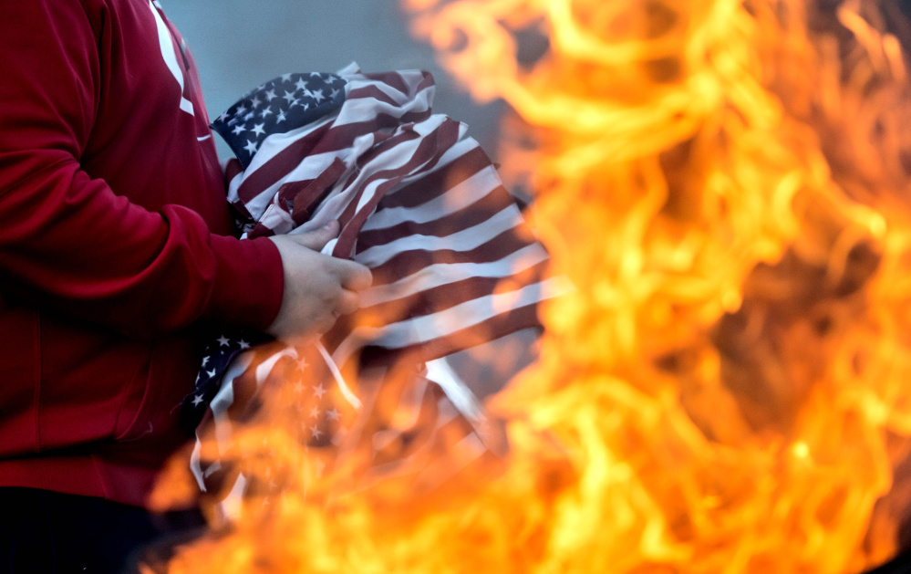 Alex Drayton retires old and tattered American flags during a ceremonial burning at the Peter-Shortier American Legion Post 16 on Saturday.