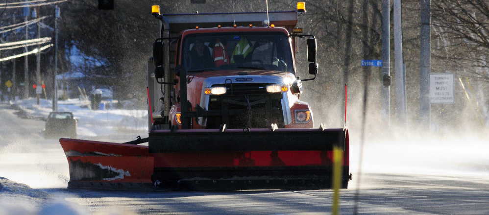 A city plow truck clears drifting snow that was covering Hospital Street on Dec. 15, 2016, in Augusta, where city staff are working to employ new strategies to help clear city streets.