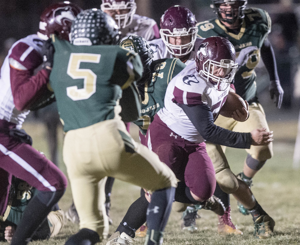 Maine Central Institute's Seth Bussell runs through the Mt. Desert Island line during the Class C North championship game Saturday night in Bar Harbor.