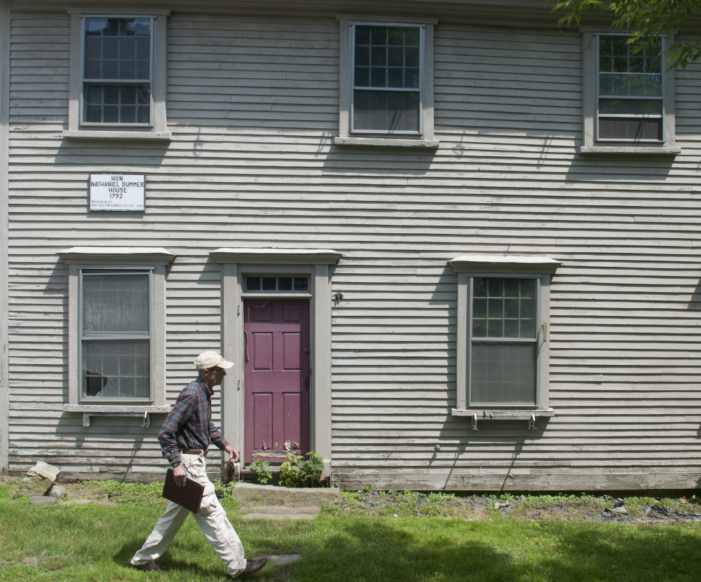Hallowell city historian Sam Webber walks past the Dummer House during an interview in June. City officials on Monday discussed a proposal to move the historic home.