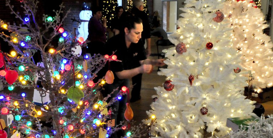 Janice Partridge, of Cappza's Pizza, decorates the company-sponsored tree at right Tuesday, next to another tree for the upcoming Sukeforth Family Festival of Trees at the Hathaway Creative Center in Waterville.
