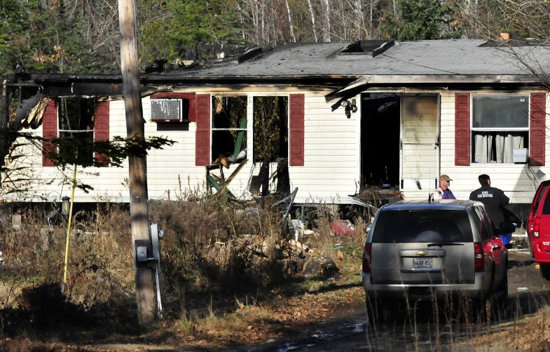 An investigator with the Office of State Fire Marshal, center, speaks with two men Wednesday outside a modular home on Pease Hill Road in Anson that a fire destroyed that morning.