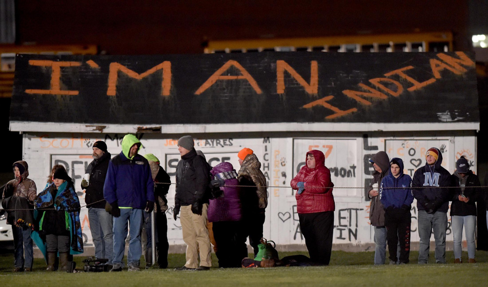 "Fans stand along the sideline of the Skowhegan Area High School football game against Lawrence High School on Friday in Skowhegan. A group of local professionals is expected to deliver a letter to the School Administrative District 54 board this evening to call for discontinuing the use of the term ""Indians"" for the school's sports teams."