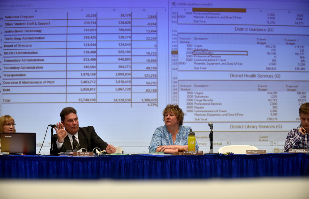 Dr. Tom Ward, left, superintendent of RSU 9 answers questions regarding the school budget during an RSU 9 budget meeting with Jennifer Zweig Hebert, right, of Starks, at Mt. Blue High School in Farmington on April 27. Tuesday the district board voted unanimously to apply to join a regional service center, a necessary step to qualify for the state to fund administration in the next few years. The district already shares services with several other districts.