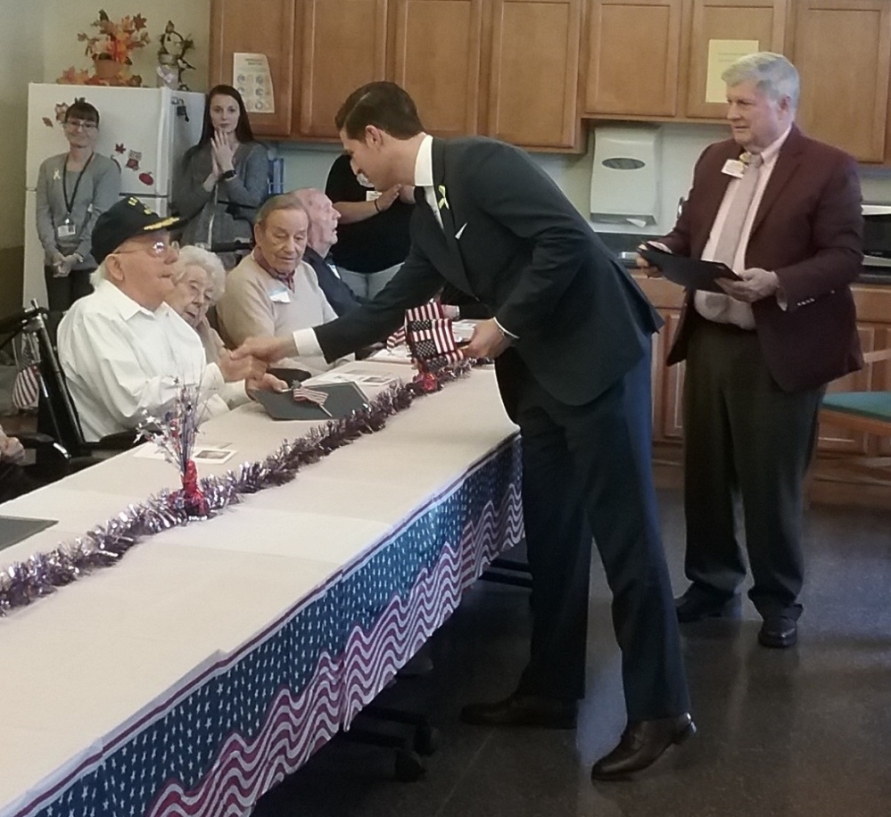 Roland Michaud, veteran of the Navy who served in WWII, shakes hands with Waterville Mayor Nick Isgro. On his left are, Yvette Mitchell, Paul Mitchell, Navy veteran, Russ Perham Army and Airforce veteran Inland Hospital president John Dalton, right, hands out certificates of recognition.