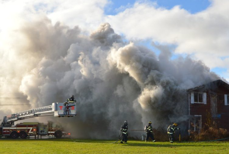Heavy wind-driven smoke hampers visibility as local fire departments battle a house fire Friday morning at 167 Morrison Hill Road in Farmington.