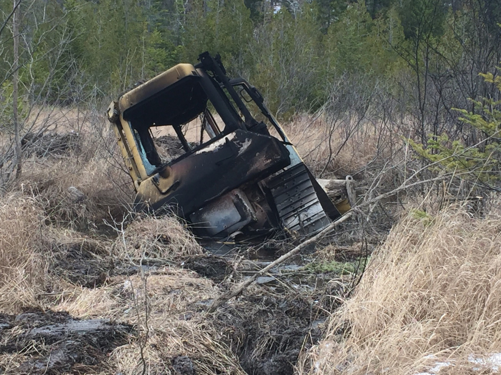 This bulldozer, owned by Cousineau Wood Products of Wilton, was found by hunters Tuesday off Beech Hill Road in Sandy River Plantation, where it had been set on fire.