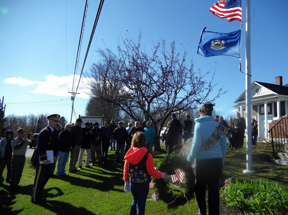 Wreath bearers Addison Poulin and Kimberly Spears bring the wreath to honor Sidney's veterans.