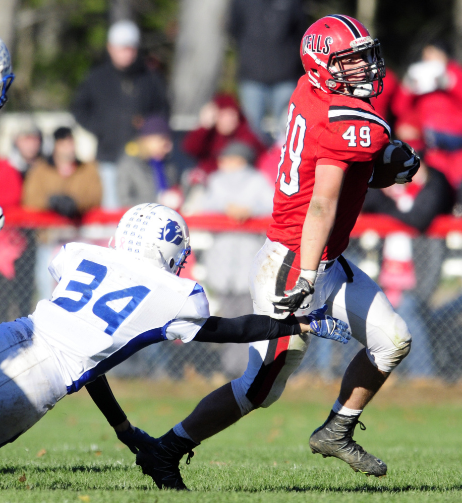 Madison's Jacob Meader, left, dives but misses Wells ball carrier Nolan Potter during the Class D South title game last Saturday in Wells.
