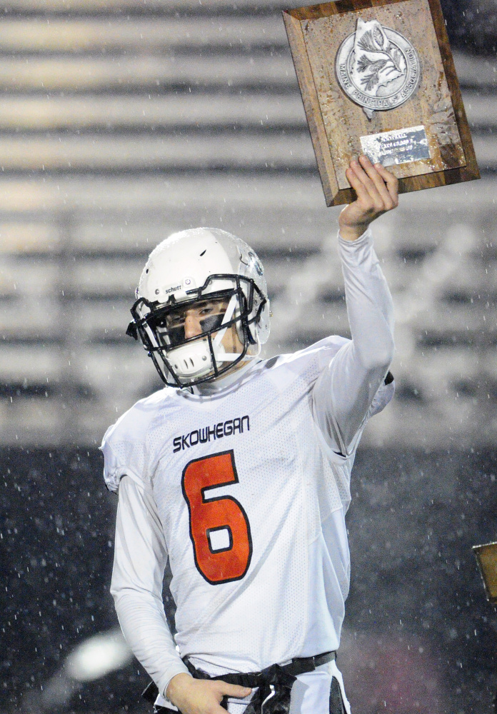 Skowhegan captain Sean Savage holds up the runnerup plaque after the Class B state game Saturday night in Portland.