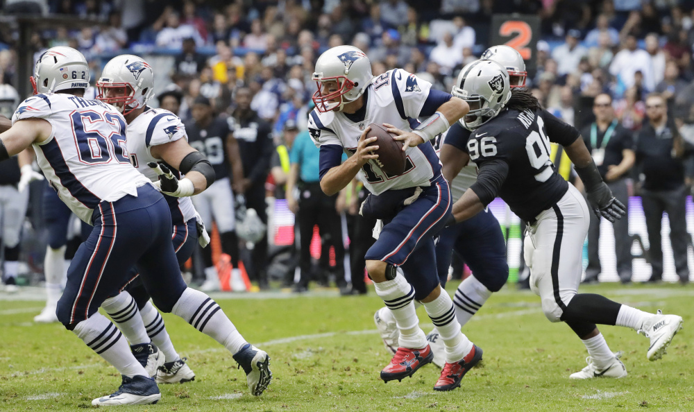 New England Patriots quarterback Tom Brady, center, scrambles against the Oakland Raiders during the first half Sunday in Mexico City.